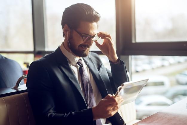 Zufriedener stilvoller lächelnder hübscher geschäftsmann im anzug, der nachrichten von einem tablett liest, während er mit kopfhörern in einem café oder restaurant sitzt.