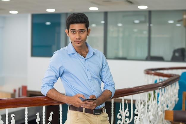 Zufriedener überzeugter junger mann, der auf geländer im modernen büro sich lehnt