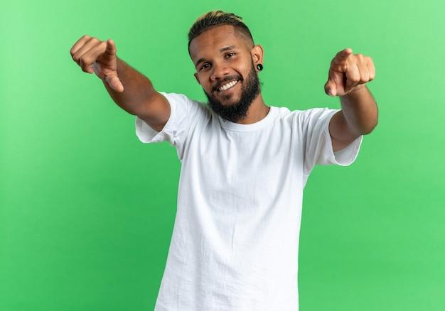 Zufriedener und glücklicher afroamerikanischer junger mann im weißen t-shirt mit blick auf die kamera, die mit den zeigefingern auf die kamera zeigt