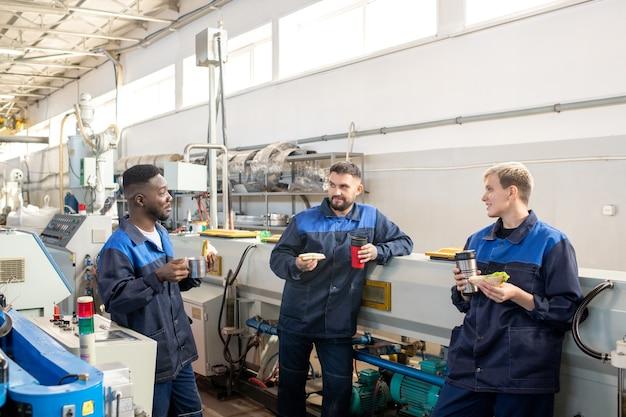 Zufriedener vorarbeiter in brillen, der den produktionsbericht mit den ingenieuren beobachtet und gleichzeitig die weitere zusammenarbeit plant