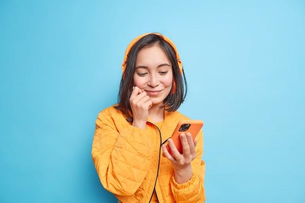 Zufriedenes asiatisches mädchen mit dunklem haar, das sich auf das smartphone-display konzentriert, wählt einen audiotrack aus der playlist und trägt drahtlose stereo-kopfhörer an den ohren, die in einer orangefarbenen jacke isoliert über blauer wand gekleidet sind