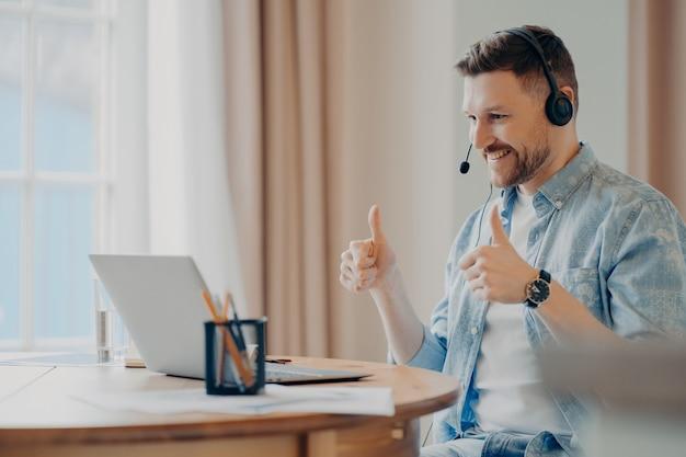 Zufriedenes bärtiges männliches model besucht online-training von zu hause aus verwendet headset macht wie eine geste mit beiden händen schaut aufmerksam auf den laptop und macht videoanrufe gegen das gemütliche interieur cozy
