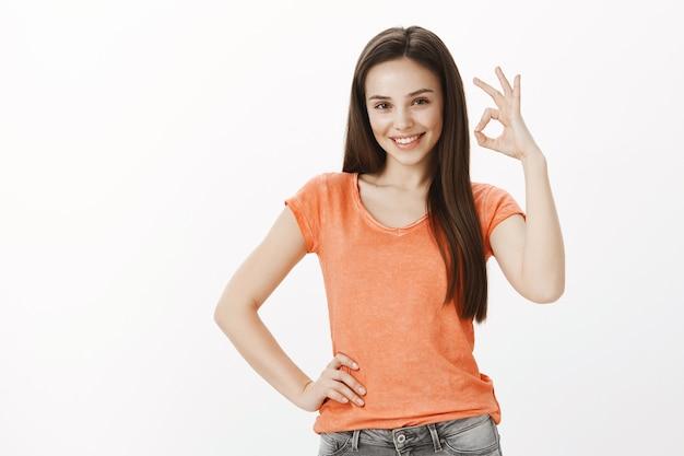 Zufriedenes fröhliches mädchen, hübsche frau, die zustimmungsgeste okay oder gut zeigt, garantieren qualität, wie idee