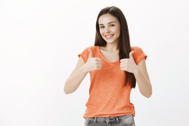 Zufriedenes fröhliches mädchen, hübsche frau, die zustimmungsgeste zeigt, daumen hoch, garantiert qualität, wie idee
