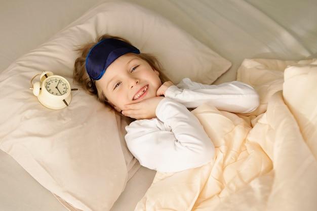 Zufriedenes glückliches kleines mädchen liegt morgens im bett und lächelt. wecker und schlafmaske.