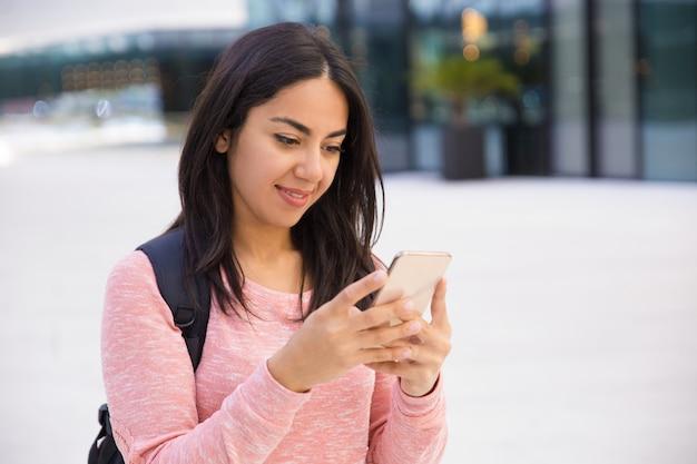 Zufriedenes hübsches studentenmädchen, das smartphone verwendet