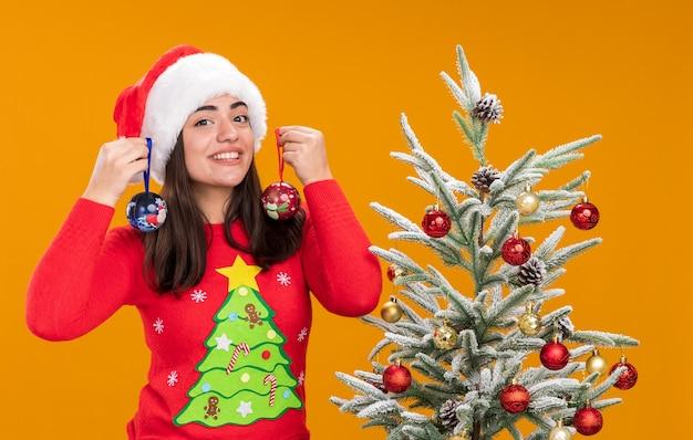 Zufriedenes junges kaukasisches mädchen mit weihnachtsmütze hält glaskugelverzierungen, die neben weihnachtsbaum stehen, lokalisiert auf orange hintergrund mit kopienraum