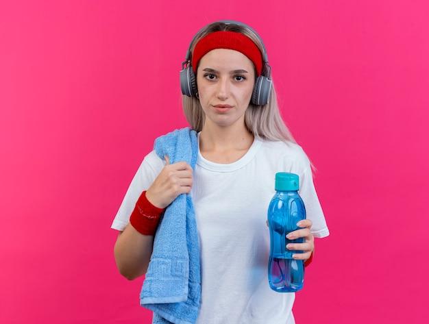 Zufriedenes junges kaukasisches sportliches mädchen mit hosenträgern auf kopfhörern mit stirnband und armbändern hält wasserflasche und handtuch auf der schulter