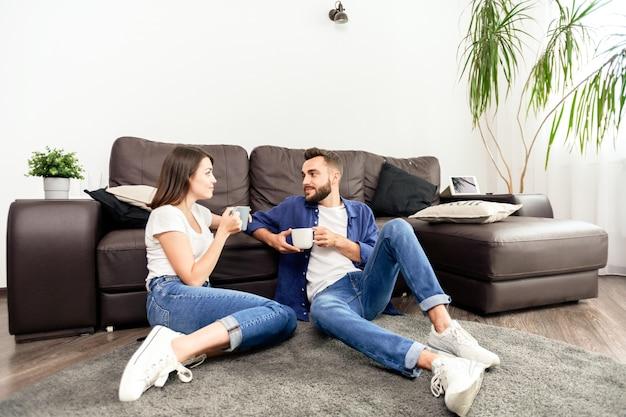 Zufriedenes junges paar in jeans und weißen schuhen, die auf teppich sitzen und kaffee trinken, während sie zeit zusammen zu hause verbringen
