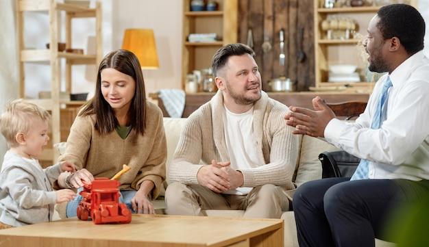 Zufriedenes junges paar mit kleinem kind, das besuch des erwachsenen schwarzen mannes hat, um immobilienhypothek zu besprechen