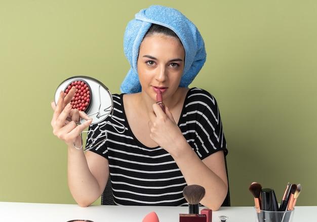 Zufriedenes junges schönes mädchen sitzt am tisch mit make-up-tools, die haare in ein handtuch gewickelt haben und lippenstift mit spiegel auf olivgrüner wand isoliert auftragen