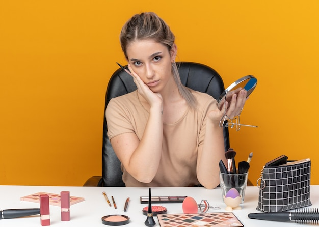 Zufriedenes junges schönes mädchen sitzt am tisch mit make-up-tools, die make-up-pinsel mit spiegel halten, die hand auf die wange legen, isoliert auf oranger wand