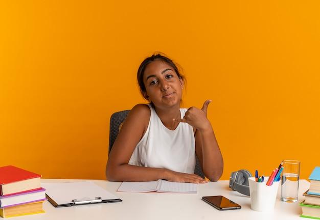 Zufriedenes junges schulmädchen, das am schreibtisch mit schulwerkzeugen sitzt, die telefonanrufgeste lokalisiert auf orange wand zeigen