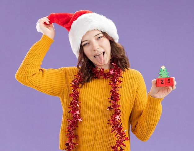 Zufriedenes junges slawisches mädchen mit weihnachtsmütze und mit girlande um hals steckt zunge heraus und hält weihnachtsbaumverzierung lokalisiert auf lila hintergrund mit kopienraum