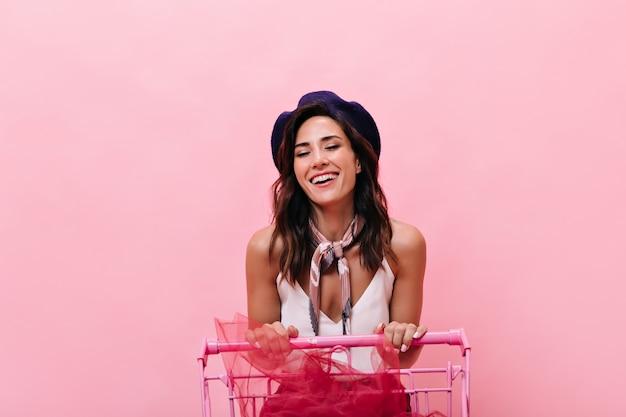 Zufriedenes mädchen lacht aufrichtig und trägt wagen auf rosa hintergrund. lächelnde frau mit welligem dunklem haar posiert und lacht in der kamera.