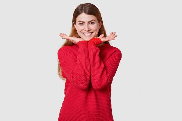 Zufriedenes mädchen mit hohem geist, weibliches modell mit glücklichem gesichtsausdruck auf weißer wand, hat angenehmes lächeln, hält hände unter kinn, trägt lässigen pullover. glückskonzept