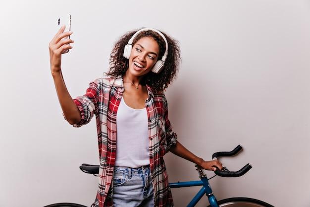Zufriedenes mädchen mit lockiger frisur, die selfie mit fahrrad macht. innenaufnahme der stilvollen afrikanischen frau, die musik auf weiß genießt