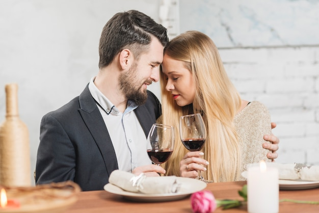 Zufriedenes paar verliebt in weingläser