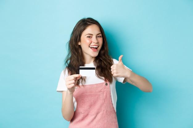 Zufriedenes schönes modernes mädchen mit plastikkreditkarte und daumen hoch, bank oder geschäft empfehlen, auf blauem hintergrund stehend
