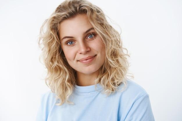Zufriedenes, sorgloses, gut aussehendes, nettes skandinavisches mädchen mit blauen augen und lockiger kurzhaarfrisur, das optimistisch lächelt und den süßen, geneigten kopf kokett als zuhört, aufrichtig in die kamera über weiße wand starrt