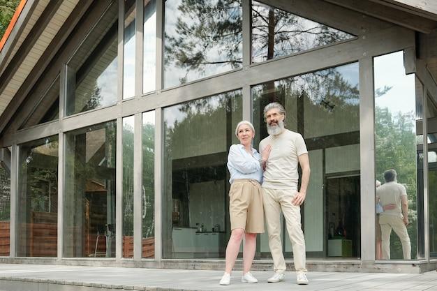 Zufriedenes stilvolles älteres paar, das gegen glashütte umarmt, während auf gäste im freien wartet