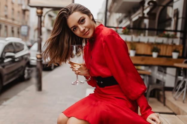 Zufriedenes, süßes mädchen lächelt sanft. rotes kleid verleiht dem outfit der dame, die mit einem glas wein posiert, helligkeit