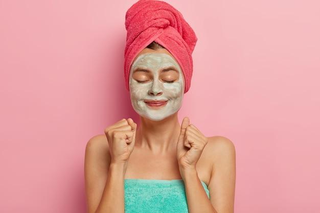 Zufriedenes weibliches model ballt die fäuste vor vergnügen, regt die durchblutung mit hilfe einer in handtuch gewickelten gesichtsmaske an, nachdem sie regelmäßig dusch- oder bademasken genommen hat. das gesicht ist frisch gereinigt