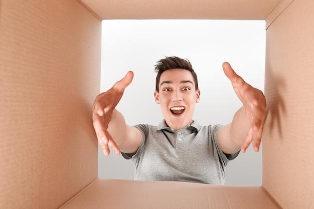 Zufriedenheit ist ein überraschter junge, der die box öffnet und in die überraschung der paketzustellung schaut