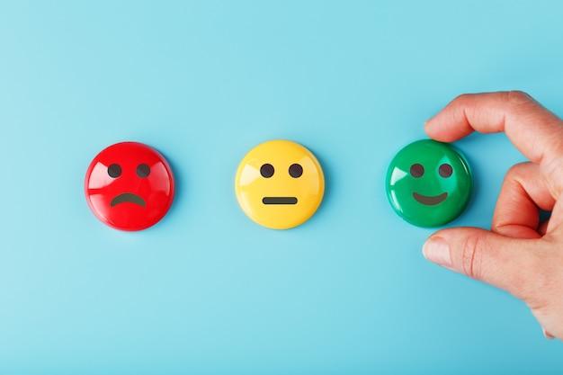Zufriedenheits-emotionssymbole roter unzufriedener, gelber neutraler und grüner lächelnder emoticon auf einer blauen oberfläche mit einer hand
