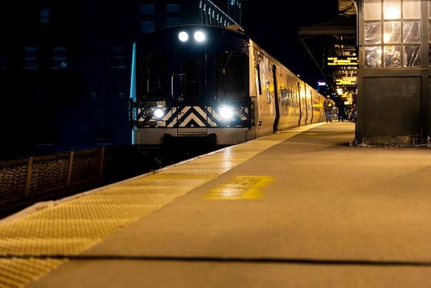 Zug fährt nachts am bahnhof vorbei