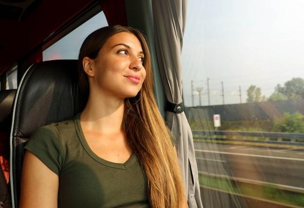 Zug- oder busreisender. schöne lächelnde frau, die durch das fenster während der reise auf öffentlichen verkehrsmitteln schaut.