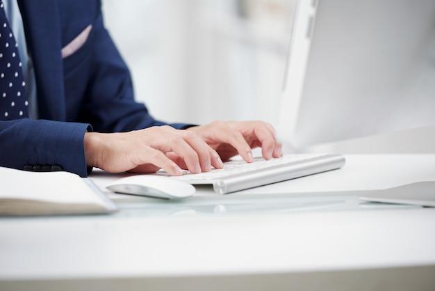 Zugeschnittener anonymer offizier, der auf weißer tastatur schreibt