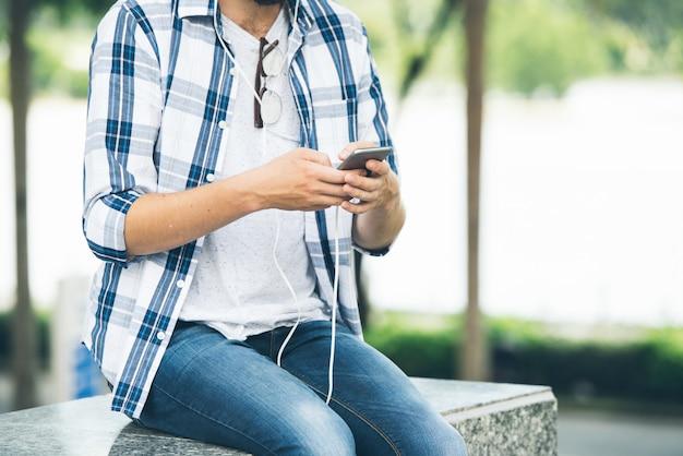 Zugeschnittener mann, der auf marmortreppen sitzt und die musik von der app einschaltet