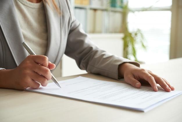 Zugeschnittener mittelteil der nicht wiedererkennbaren frau, die das dokument unterzeichnet