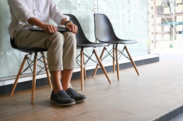 Zugeschnittener schuss mannwarteinterview, das auf stuhl sitzt.