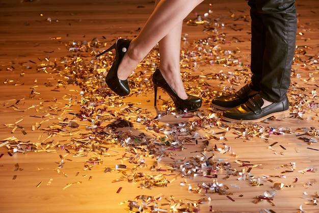 Zugeschnittener schuss von weiblichen und männlichen füßen auf die party
