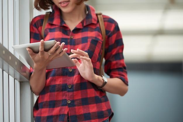 Zugeschnittener student, der die bildungsanwendung auf ihrem tablet-pc am college verwendet