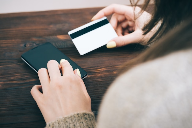 Zugeschnittenes bild einer frau gibt informationen von einer kreditkarte in ihr smartphone ein