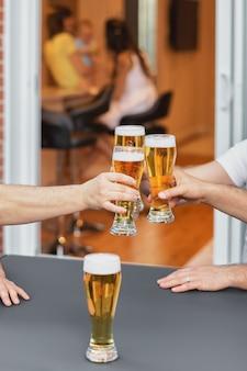 Zugeschnittenes bild hände einer gruppe von stimmhaften gläsern bier, partys und feiern.
