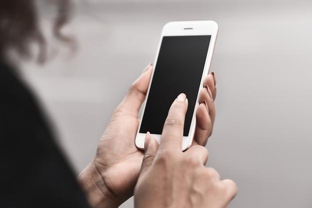 Zugeschnittenes bild von frauenhänden, die ein smartphone mit leerem bildschirm für textnachrichten halten