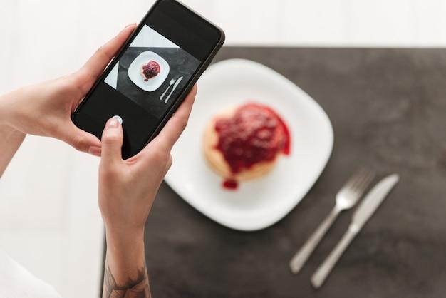 Zugeschnittenes foto der frau machen foto von pfannkuchen telefonisch.