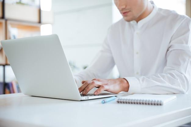 Zugeschnittenes foto eines jungen mannes in weißem hemd mit laptop-computer. coworking.