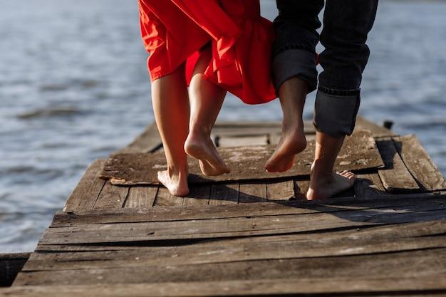 Zugeschnittenes foto junges liebespaar, mann und frau, die hände auf einer holzbrücke in der nähe des sees halten. rückansicht des paares, das auf pier steht. untere hälfte. platz für text und design. nahaufnahme.