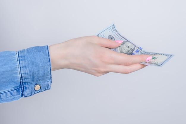 Zugeschnittenes nahaufnahmeseitenprofil-fotoporträt von händen, die 100 dollar auf grauem hintergrund zeigen