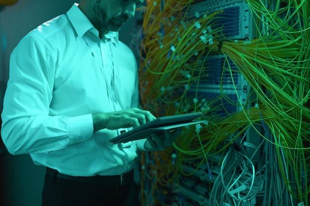 Zugeschnittenes porträt eines gutaussehenden dateningenieurs mit digitalem tablet im serverraum, während er mit supercomputer in blauem licht arbeitet, kopierraum