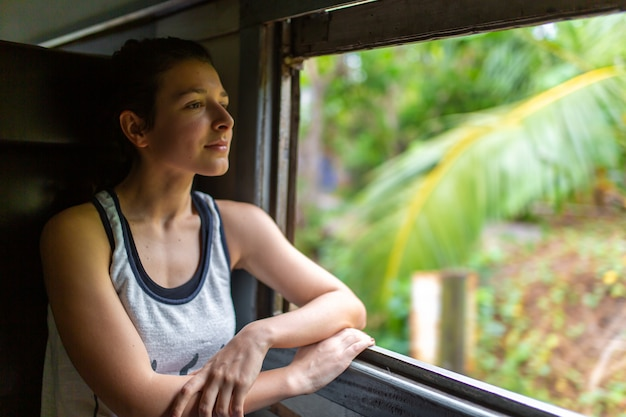 Zugfahrt in sri lanka. frau sitzt und schaut aus dem fenster