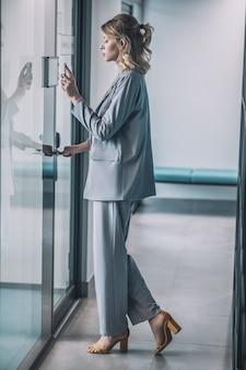 Zugriffskontrollsystem. junge schlanke frau im geschäftsanzug mit hohen absätzen, die im korridor vor ihrer bürotür stehen
