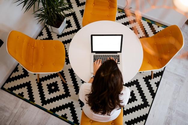 Zuhause arbeiten. draufsicht der frau, die laptop im modernen, gemütlichen raum verwendet.