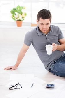 Zuhause arbeiten. draufsicht eines selbstbewussten jungen mannes, der eine tasse hält und die dokumente betrachtet, während er in seiner wohnung auf dem boden sitzt