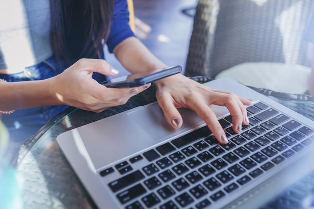 Zuhause arbeiten. frau sms eine massage auf dem handy und netzwerkverbindung mit dem laptop.
